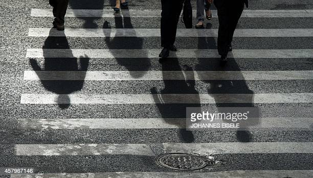 Commuters cast their shadow while walking across a street in Pudong's Lujiazui Financial District in Shanghai on October 28 2014 The Chinese economy...