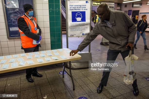Commuters collect free face masks as they use the London Underground on June 8, 2020 in London, United Kingdom. As the British government further...