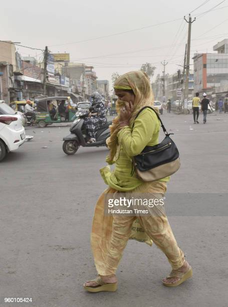 Commuters cover their face as they walk during a sudden dust storm on May 19 2018 in Gurugram India The capital was in for some relief from rising...