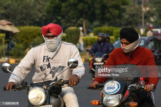 Commuters cover their faces to protect themselves from the air pollution in the city on November 20 2019 in New Delhi India After three days of...