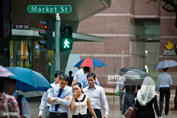 Commuters cross a road in the central business district of Singapore on Wednesday Oct 28 2015 Singapore's third quarter unemployment rates are...