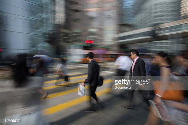 Commuters cross a street in the business district of Central in Hong Kong China on Tuesday Oct 15 2013 The Government is scheduled to release...