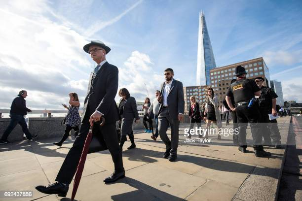 Commuters cross London Bridge after it was reopened following the June 3rd terror attack on June 5 2017 in London England Seven people were killed...
