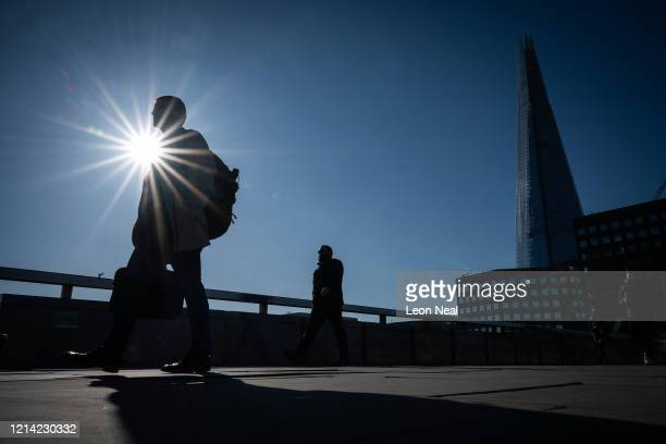 Commuters cross London Bridge at around 830am during what would usually be the busy morning rush hour period on March 23 2020 in London United...