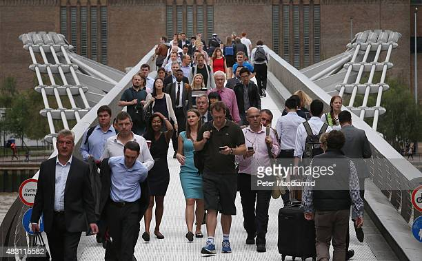 Commuters cross The Millennium bridge over the River Thames on August 6 2015 in London England London Underground workers are staging another 24 hour...