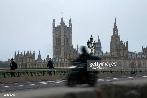 Commuters cross Westminster Bridge in view of the Houses of Parliament on December 7, 2020 in London, United Kingdom. After a weekend of tense talks,...
