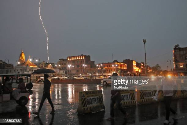 Commuters crosses a road as it rains during a lightning strike in the sky in Jaipur, Rajasthan, India, July 11,2021.