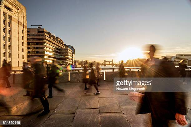 commuters crossing london bridge - incidental people stock pictures, royalty-free photos & images