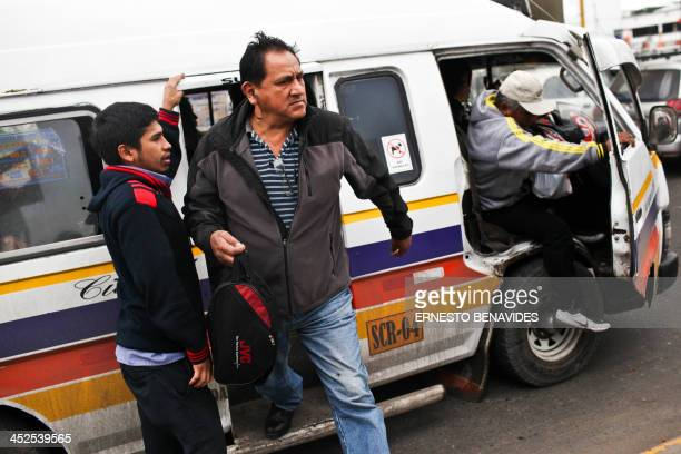 Commuters disembark from a combi minibus in Lima on November 29 2013 Lima's combis drive along the streets of Lima at high speed do not respect the...