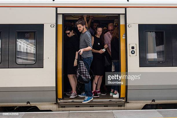 Commuters disembark from a crowded train operated by GoAhead Group Plc's SouthEastern railway franchise on a newly opened platform at London Bridge...