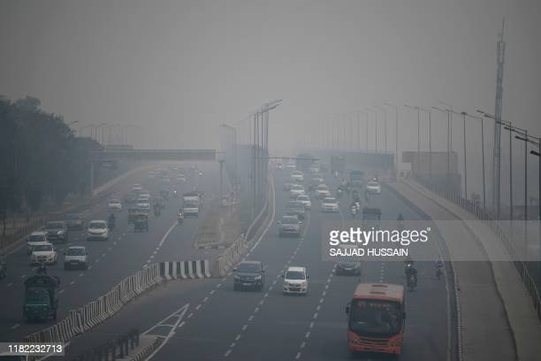 TOPSHOT Commuters drive along a motorway under heavy smog conditions in New Delhi on November 14 2019