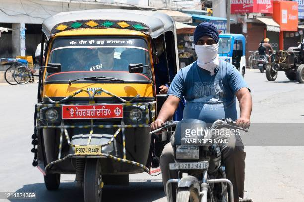 Commuters drive along a road during a hot day after the government eased a nationwide lockdown imposed as a preventive measure against the COVID19...