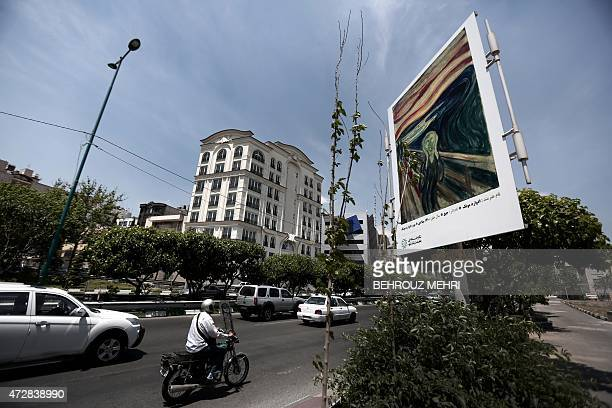 Commuters drive past a billboard displaying a reproduction of 'The Scream' painting by Norwegian Expressionism pioneer Edward Munch on north Tehran's...