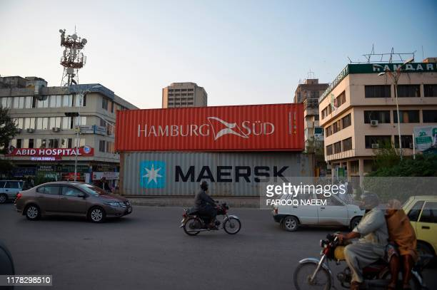 Commuters drive past containers placed on roadside in Islamabad on October 26 ahead of opposition party Jamiat UlemaeIslam antigovernment protest ...