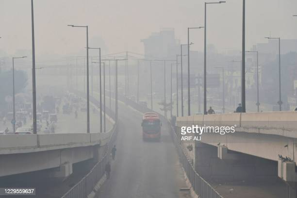 Commuters drive their vehicles amid heavy smoggy conditions in Lahore on November 10, 2020.