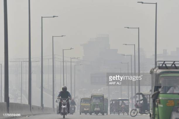 Commuters drive their vehicles on a bridge amid heavy smoggy conditions in Lahore on November 10, 2020.