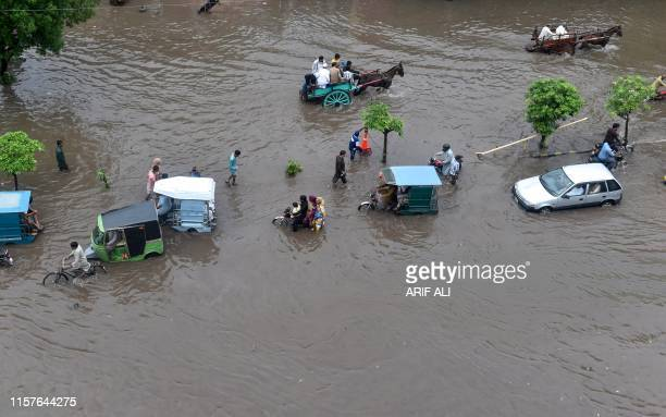 Commuters drive through a flooded street during heavy monsoon rains in Lahore on July 25, 2019.
