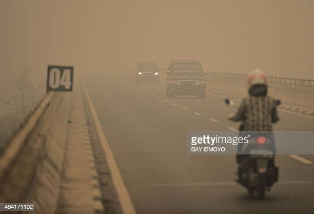 Commuters drive through thick haze in Tumbang Nusa Central Kalimantan on October 25 2015 Indonesia has put warships on standby to evacuate people...