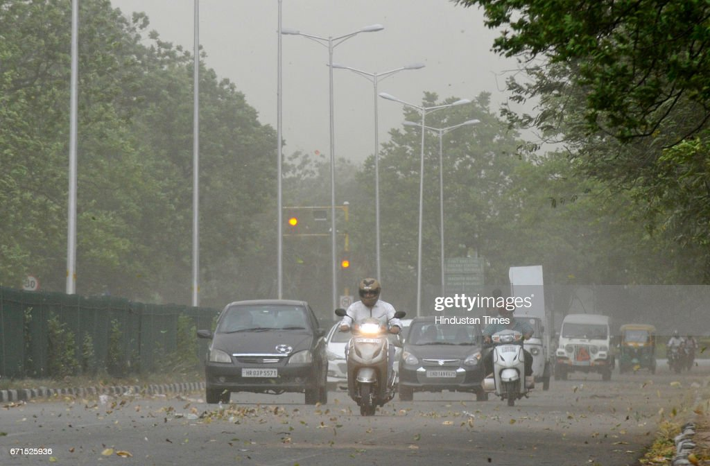 Commuters driving during the dust storm and strong winds on April 22 2017 in Chandigarh India The storm led to trees falling in some areas power cuts.