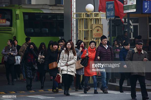 Commuters exit a bus terminal in the central business district of Beijing China on Friday March 6 2015 China set the lowest economic growth target in...