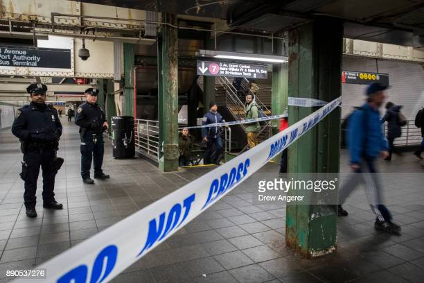 Commuters exit a train as police officers stand in a closedoff underground walkway near the site of a pipe bomb explosion in the tunnel that connects...