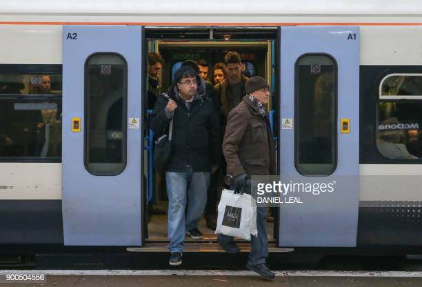Commuters exit a train at Victoria station, in central London on January 2, 2018. - As the price of an average ticket rose by 3.4 percent on January...