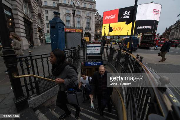Commuters exit Picadilly Circus underground station as the Piccadilly Circus lights are switched back on after a nine month renovation on October 26...