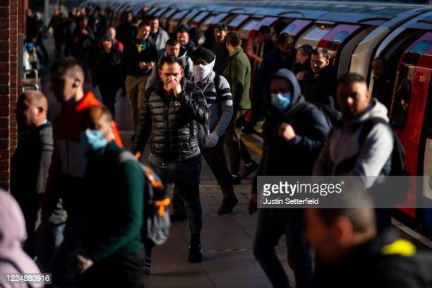 Commuters exit the tube at West Ham station in East London on May 14, 2020 in London, England. The prime minister announced the general contours of a...