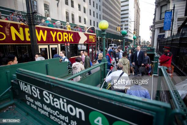 Commuters exit the Wall Street subway station near the New York Stock Exchange in New York US on Tuesday April 11 2017 US stocks slid as investors...