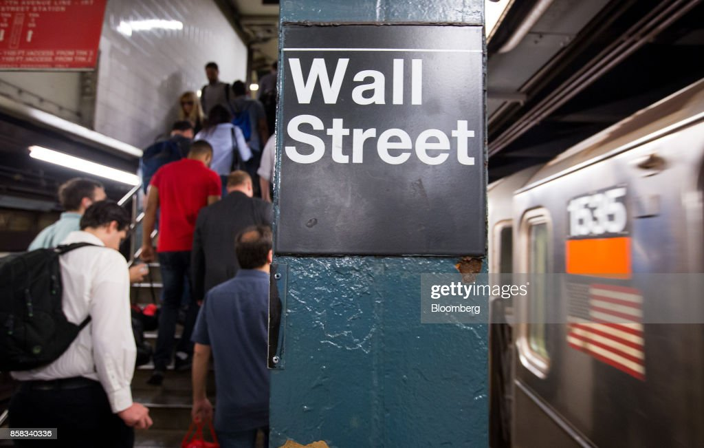 Commuters exit the Wall Street subway station near the New York Stock Exchange (NYSE) in New York, U.S., on Friday, Oct. 6, 2017. U.S. stocks edged lower while the dollar rose with Treasury yields after American payrolls contracted for the first time since 2010 and hourly wages spiked higher. Photographer: Michael Nagle/Bloomberg via Getty Images