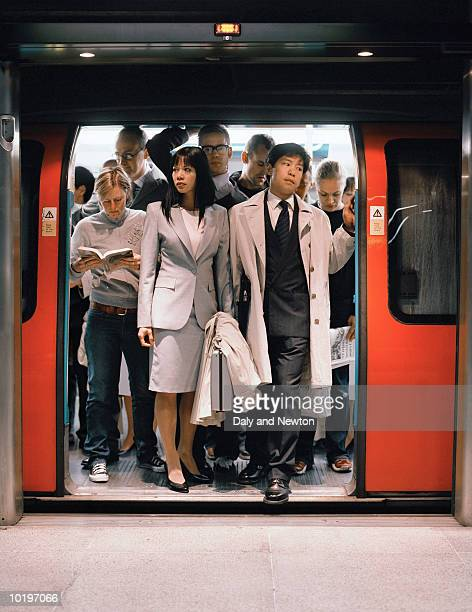 commuters exiting underground train - affollato foto e immagini stock