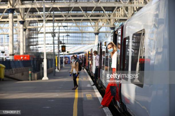 Commuters get off a train walk after arriving at London Waterloo railway station, on so-called 'Freedom Day', in London, U.K., on Monday, July 19,...