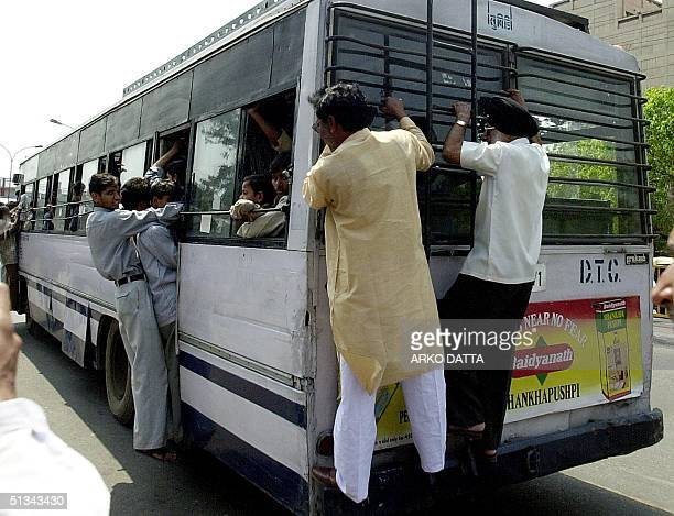 Commuters hang from an overcrowded bus in New Delhi 01 April as most of the buses stayed off the road in line with India's Supreme Court's 1998...