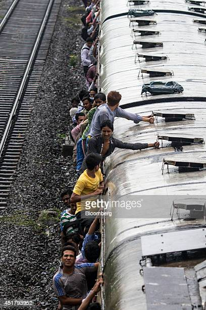 Commuters hang from the roof and doorways of a train during the morning rush hour in Mumbai India on Friday July 4 2014 Indian Railways' annual...