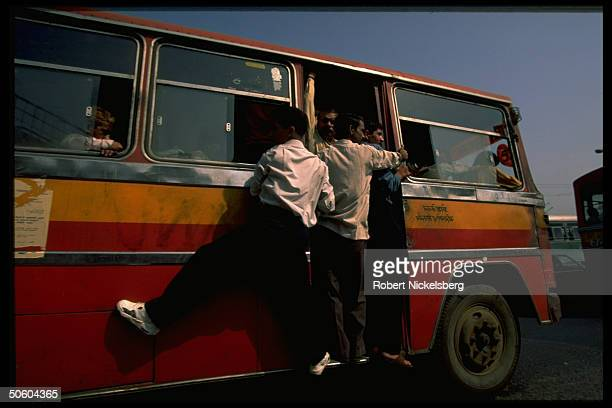 Commuters hanging off crowded Red Line bus, privately owned & run transport system notorious for up to 300 deaths per yr. Of people entering &...
