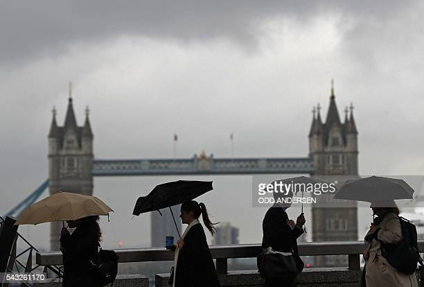 TOPSHOT Commuters heading into the City of London walk across London Bridge in front of Tower Bridge in central London on June 27 2016 Britain should...