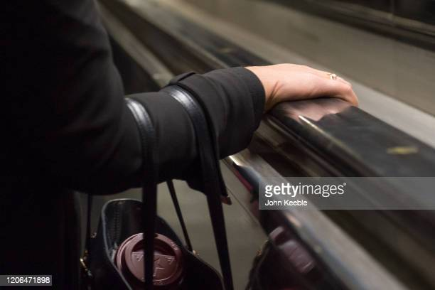 Commuters hold on to the handrail of a escalator on March 10, 2020 in London, England. It has been reported that a person could also contract the new...