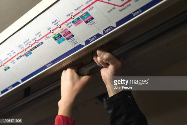 Commuters hold on to the handrail on a tube train on March 10 2020 in London England It has been reported that a person could also contract the new...