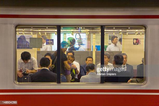 Commuters in Tokyo subway carriage waiting for departure.