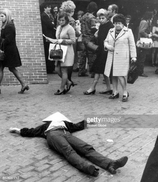 Commuters leaving the MTA station at City Hall Plaza in Boston are stunned by a man pretending to be wounded on the ground to protest the Vietnam War...