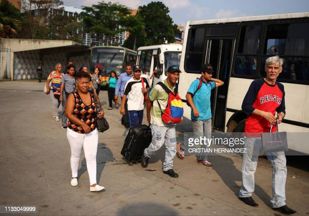 Commuters line up to board buses enabled for transportation after a blackout disabled the CaracasCharallave railway in Caracas on March 26 2019...