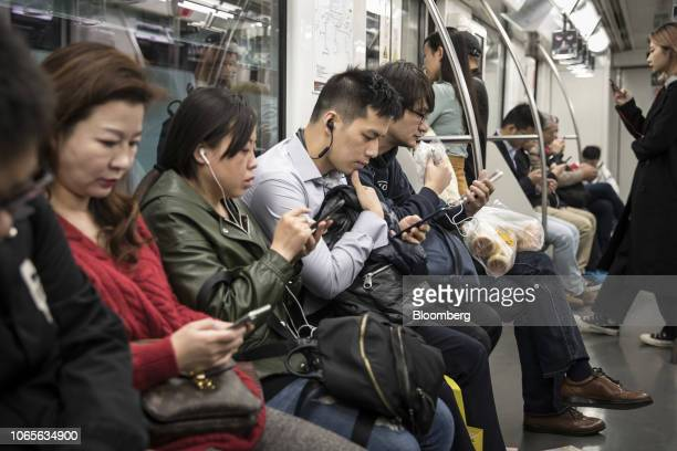 Commuters look at the smartphones on a subway train in Shanghai China on Tuesday Nov 27 2018 Apple which has lost a fifth of its value in a tech...