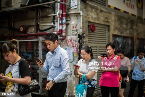 Commuters look at their mobile phones as they wait in line for a bus after finishing work in Hong Kong on June 1 2016 / AFP / ANTHONY WALLACE