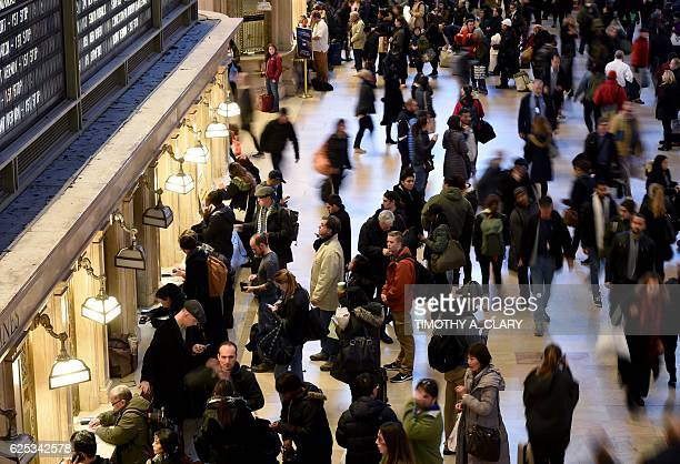 Commuters look at train schedules as people make their way home at Grand Central Station in New York on November 23 2016 on the day before...