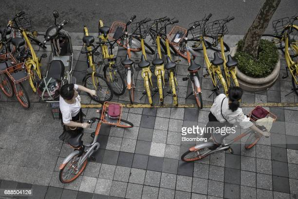 Commuters look for parking spaces for their Mobike bicycles near parked Ofo Inc. And Mobike bikes on a sidewalk in Shanghai, China, on Thursday, May...