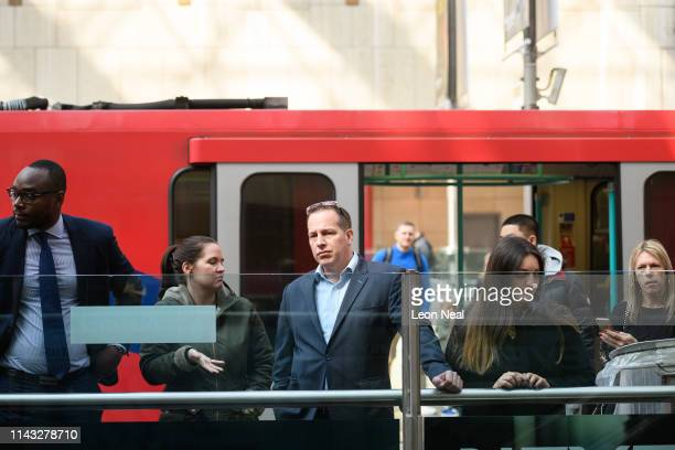 Commuters look on as environmental campaigners from the Extinction Rebellion group block a DLR train at Canary Wharf staion on April 17 2019 in...