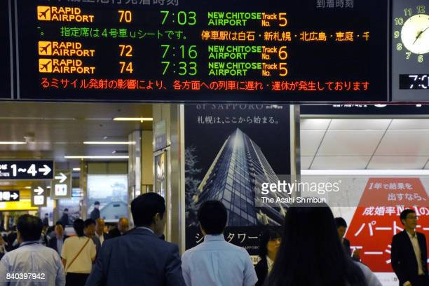 Commuters look up a monitor displaying the delay of train due to North Korea's missile launch over Hokkaido at JR Sapporo Station on August 29 2017...