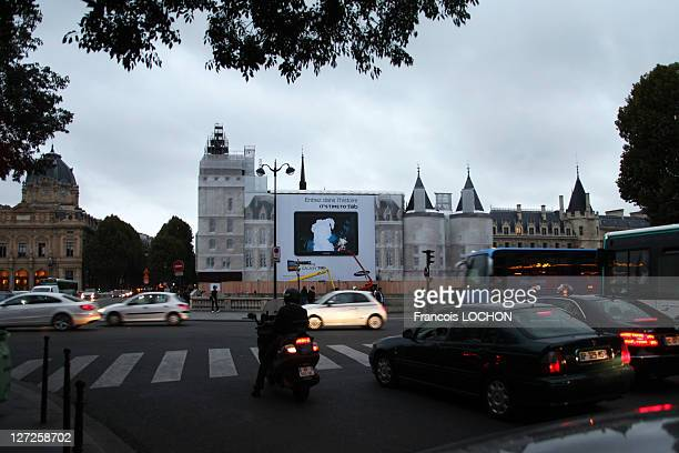 Commuters make their past an advertisement featuring the image of MarieAntoinette on the wall of the Conciergerie on September 26 2011 in Paris...