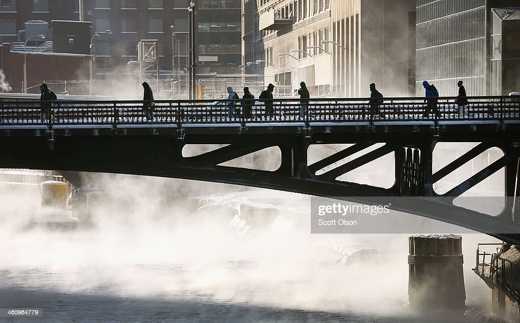 Commuters make their way across the Chicago River during a sub-zero trek to their offices in the Loop on January 6, 2014 in Chicago, Illinois. Temperatures in some areas of the city dipped to -16 during the morning commute. A polar vortex sweeping through the Midwest has brought dangerously cold temperatures not seen in about 20 years.