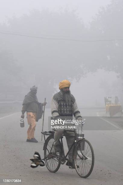 Commuters make their way along the road amid dense fog on a cold winter morning near the India-Pakistan Wagah Border Post, some 35 km from Amritsar...